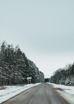 Дорога зимой. красивая дорога у леса. зимний пейзаж. пустая дорога