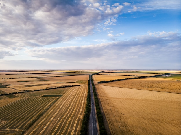 Road inside the fields. sky with clouds from the aerial view