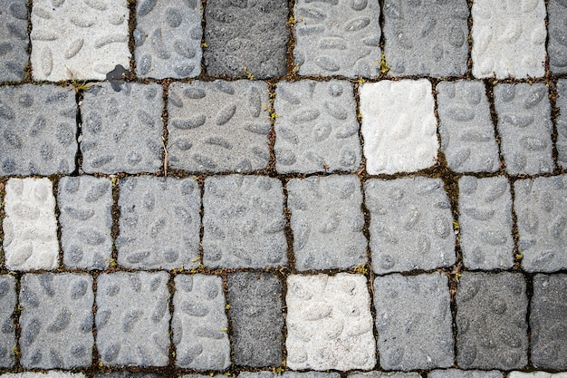 The road is paved with gray stones, top view. stone texture, outdoor stone tiles
