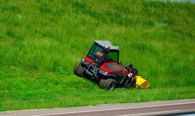 Дорожный ландшафтный дизайнер стрижет траву по улице