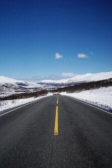 Road leading to beautiful snowy mountains