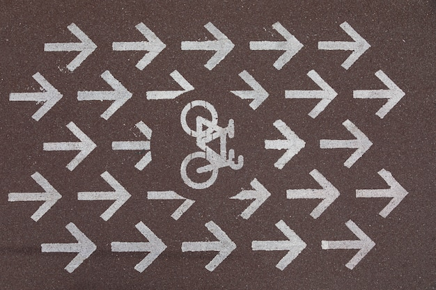 회색 아스팔트에 오른쪽을 가리키는 화살표가있는 도로 표시 자전거 차선