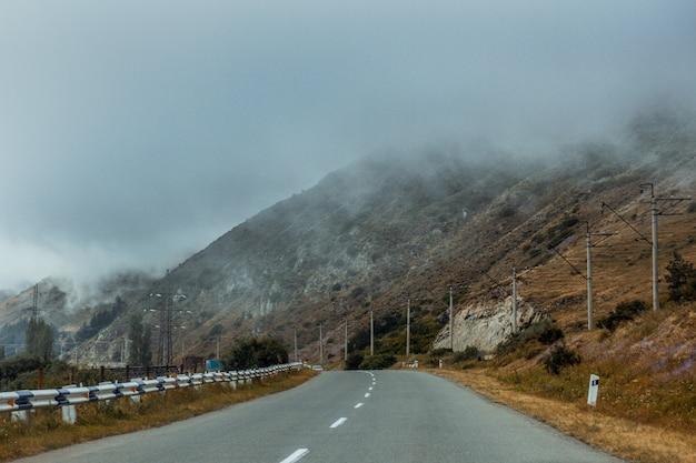 Road near high mountains enveloped in fog