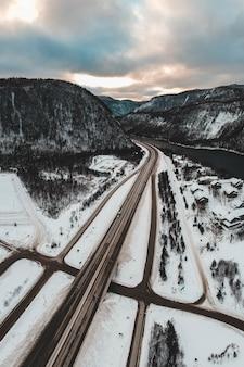 昼間は雪に覆われた川と山の近くの道路