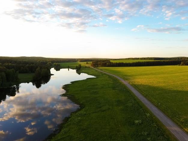 日没時の夏の日の川と森の近くの道路。ドローンからの眺め。