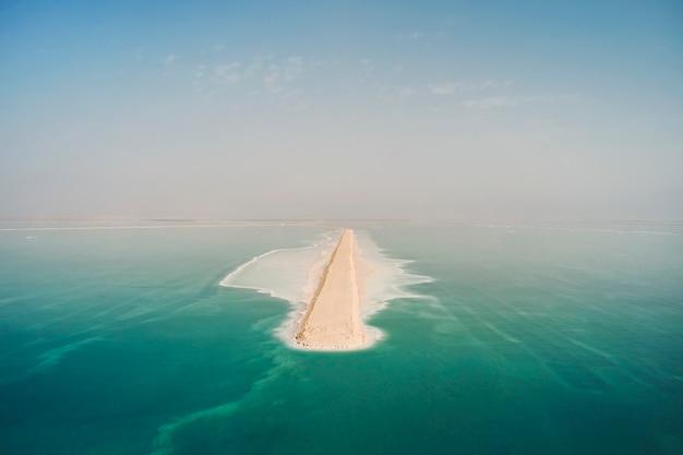 사해 표면에 도로입니다. 사해의 남쪽 부분은 미네랄을 추출하는 웅덩이로 나뉩니다. 해안은 사해의 푸른 바닷물에 씻겨진 하얀 소금 결정으로 덮여 있습니다.