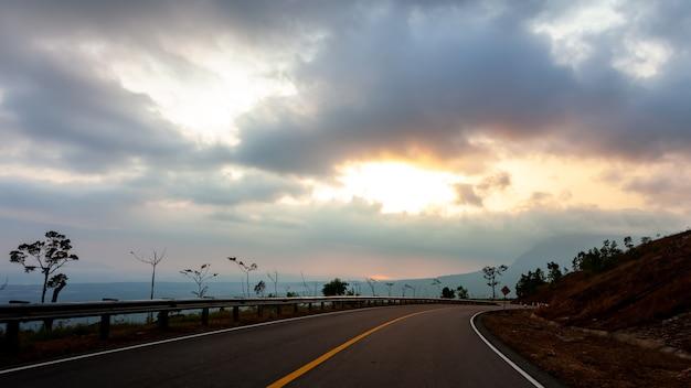風景の夕日を望む山の道