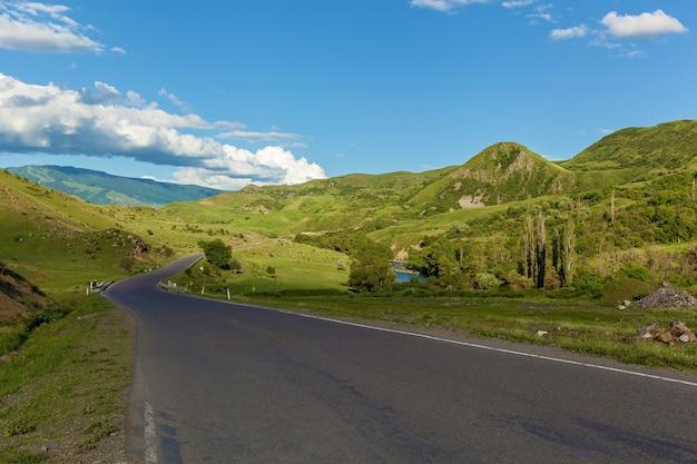 緑の牧草地の山々と空を背景にした道路背景にある道路