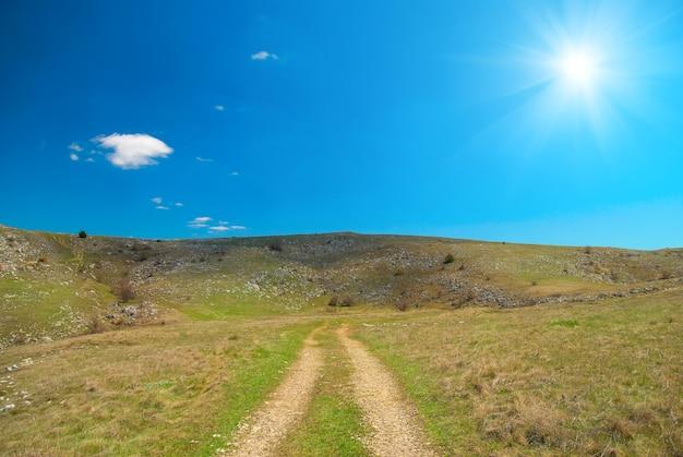 雲景と輝く太陽のある丘の上の道。