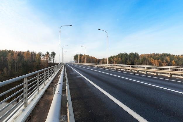 Дорога, проходящая по мосту через реку. снимок был сделан крупным планом в осенний сезон. видно голубое небо и светящиеся ночью столбы.