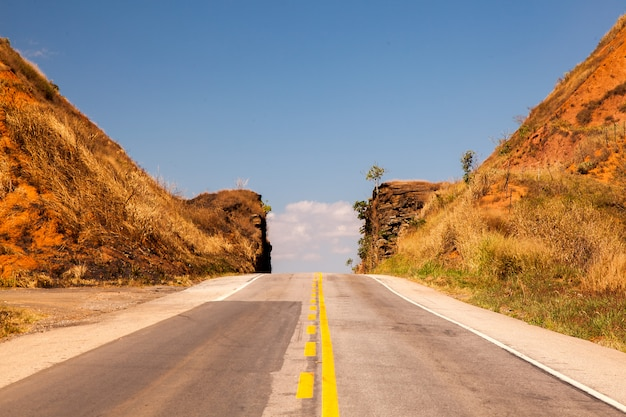 Road passing through narrow cutted rock with blue sky
