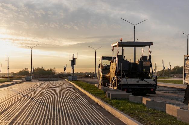 Ремонт дорог и мощение асфальта специализированной машиной вечером на фоне закатного неба. вечером асфальтоукладчик ремонтирует дорожное покрытие.