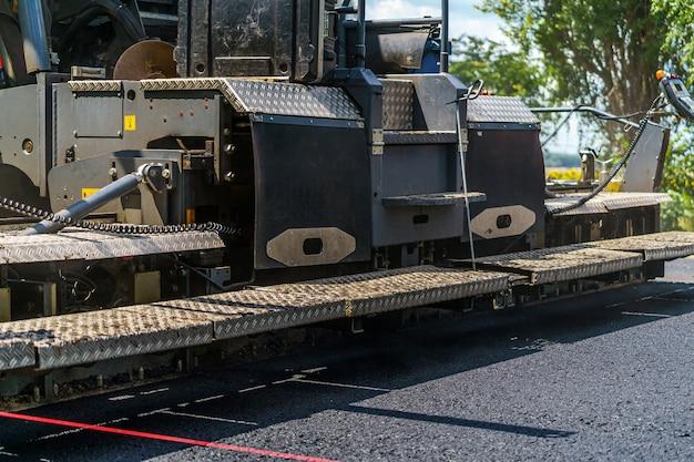 Ремонт дорог, компактор укладывает асфальт. тяжелые специальные машины. асфальтоукладчик в эксплуатации. вид сбоку. крупный план.