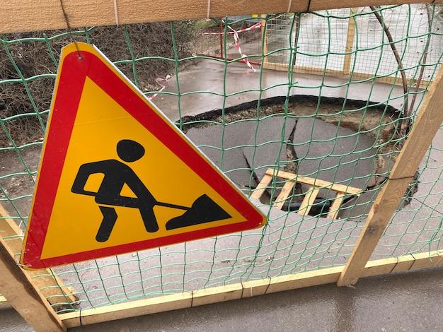 Знак ремонта дороги катастрофическое разрушение асфальта дороги глубокие ямы в полотне большая яма, окруженная забором, плохая технология строительства дороги и тротуаров