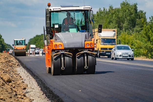 新しいアスファルトを平らにするロードローラー。アスファルト舗装、道路補修中の重振動ローラー。セレクティブフォーカス。