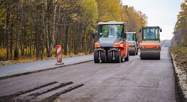 Дорожный каток выравнивает новый асфальт. тяжелый вибрационный каток на работе, мощение асфальта, ремонт дорог. выборочный фокус.