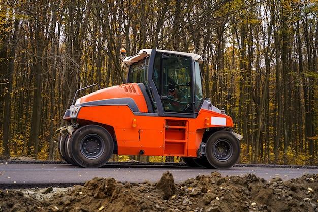 新しいアスファルトを平らにするロードローラー。アスファルト舗装、道路補修中の重い振動ローラー。セレクティブフォーカス。