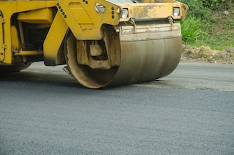 Road roller machine works on the fresh asphalt, Asphalt road construction