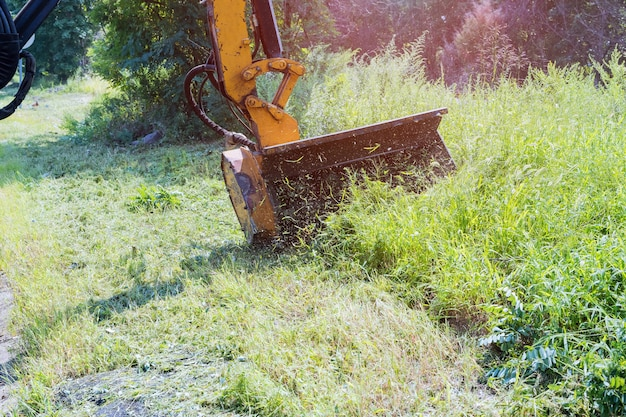 Road services are engaged in tractor with a mechanical mower mowing grass on the side of the asphalt road landscaping around roads