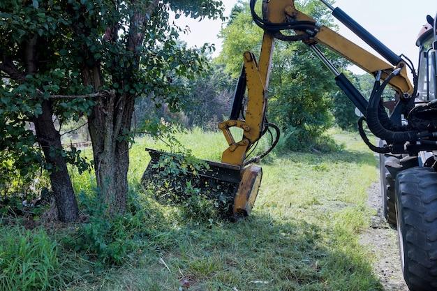 アスファルト道路の脇に草刈り機を備えたトラクターの道路周辺の造園道路サービス