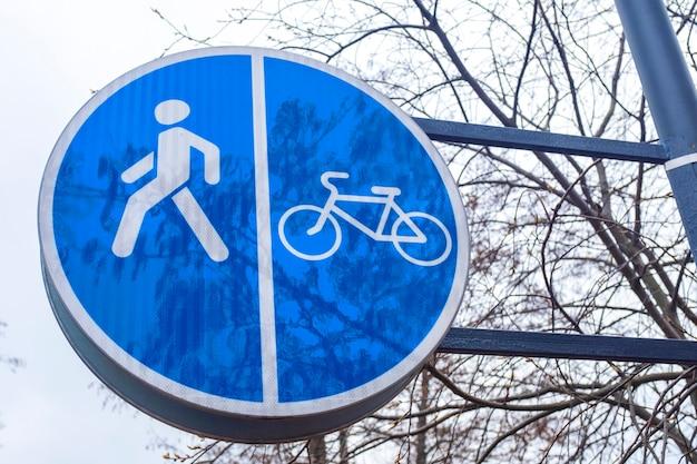 Дорожный знак синий круг с велосипедом и фигурой человека. велосипедные и пешеходные дорожки.