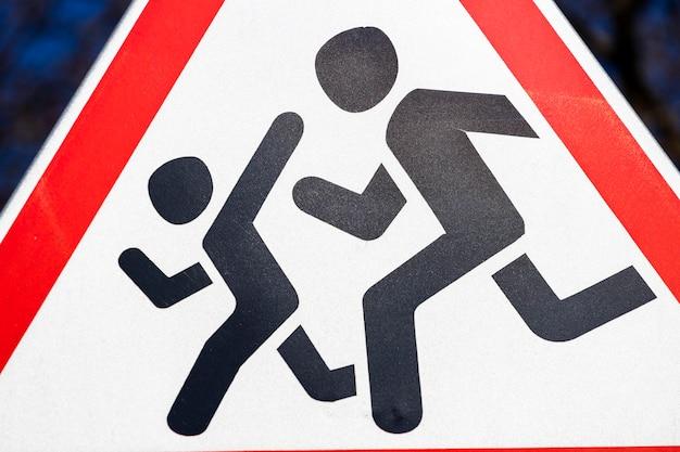 Дорожный знак осторожные дети. предупреждение водителя о бегущих людях.