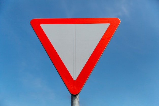 Road sign give way on blue sky