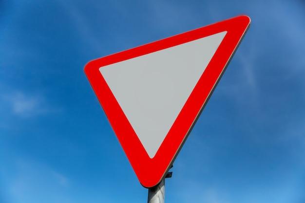 道路標識は青空の背景に道を譲る
