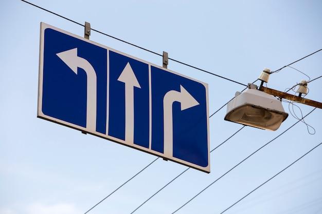 方向を示す青色の背景に3つの白い矢印が付いている通りに高い道路標識。