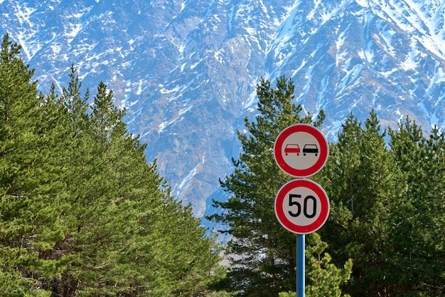 制限速度の道路標識と曲がりくねった山道での追い越しの禁止。危険な高山道路。
