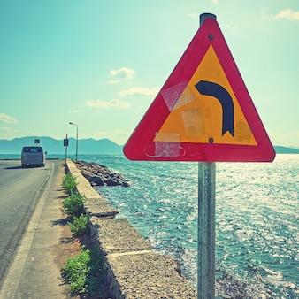 Дорожный знак на углу дороги у моря. винтажный стиль тонированное изображение