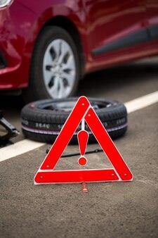壊れた車、スペアタイヤ、工具を背景にした道路標識