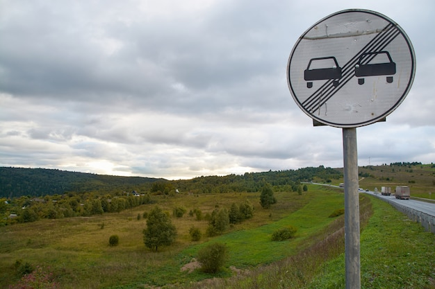 Дорожный знак на фоне гор и облачного неба.