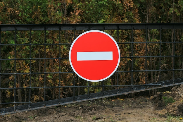 Road sign prohibition on a metal gate over a dark forest