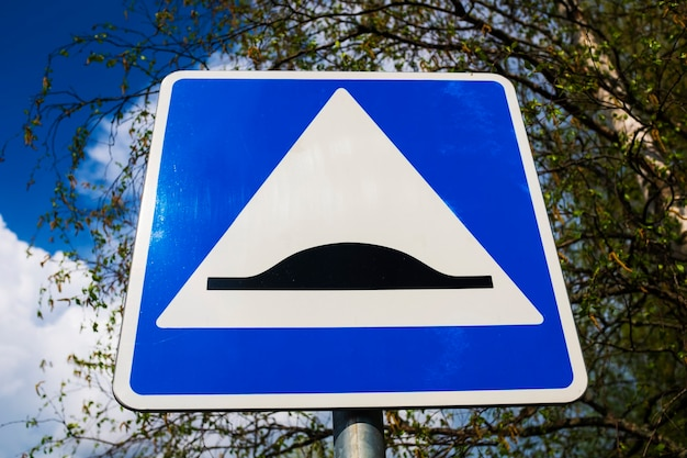 道路標識のスピードバンプ。白い三角形と黒い障害物と青い正方形。高品質の写真