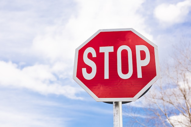 Road sign stop on a cloudy sky