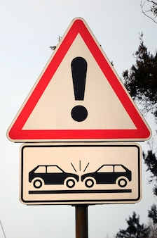 A road sign with an exclamation point and two cars that crashed into each other