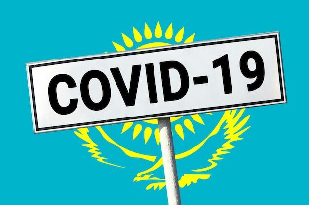 Дорожный знак со словом covid19 на фоне флага республики казахстан