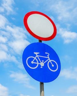 Дорожные знаки на фоне неба, транспорт закрыт и велосипедисты