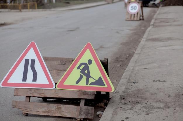 Дорожные знаки, объезд, ремонт дорог на фоне улиц, яма для грузовика и экскаватора