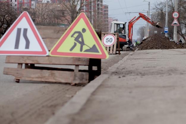 도로 표지판, 우회, 도로 수리, 트럭 및 굴삭기 파기 구멍.