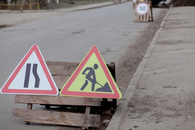 Road signs, detour, road repair on street background, truck and excavator digging hole