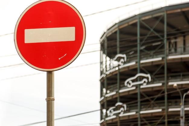 マルチレベルの駐車場の背景に一時停止の標識。丸い道路標識-赤に白のストライプ。駐車場に入る車に警告する道路標識の底面図