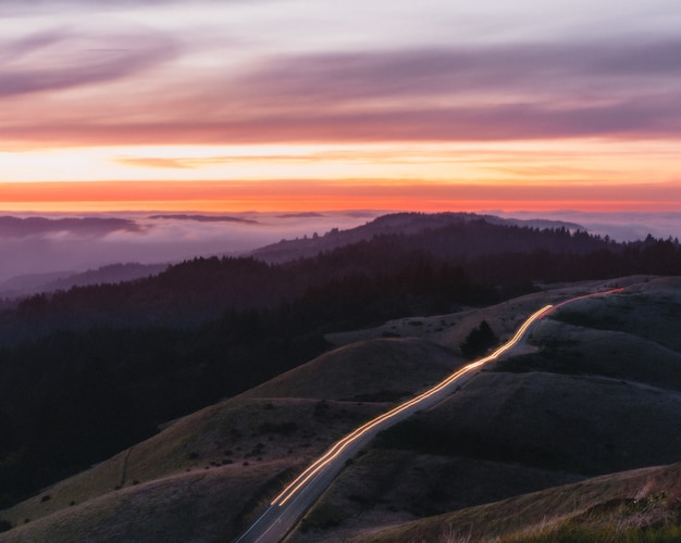아름다운 일몰 동안 긴 노출로 언덕과 빛으로 둘러싸인 도로
