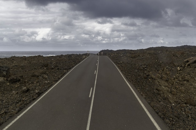 Road surrounded by hills under a cloudy sky in the timanfaya national park in spain