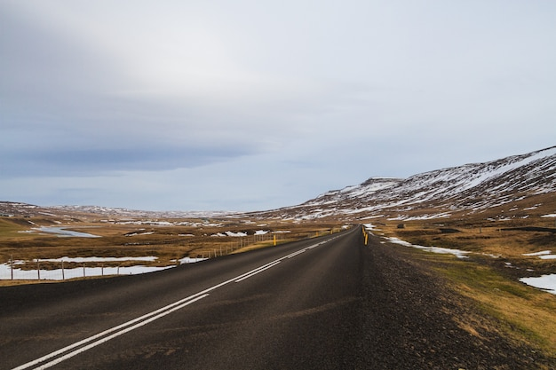 Road surrounded by hills covered in the snow and greenery under a cloudy sky in iceland