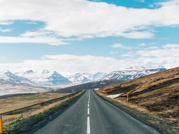 Дорога в окружении холмов со скалистыми горами, покрытыми снегом