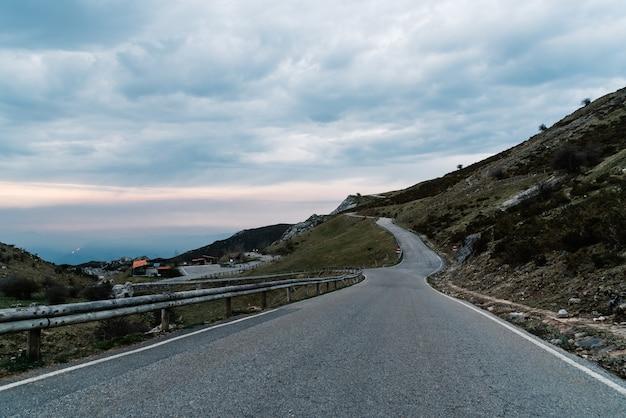 夕方の曇り空の下で山々に囲まれた道