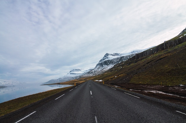 Strada circondata dal fiume e dalle colline coperte di neve ed erba sotto un cielo nuvoloso in islanda