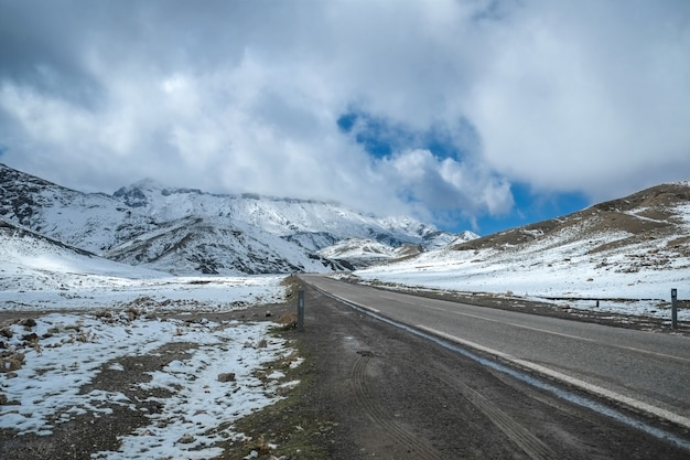 A road surrounded by snow capped mountains in the high atlas range. morocco.